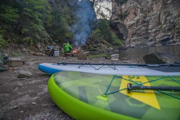 Two kayaks in the foreground with a man making a fire in the background
