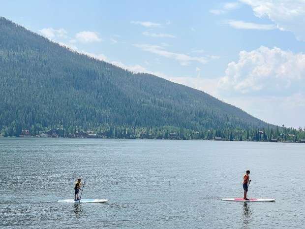 Paddleboarders enjoy the calm waters of Grand Lake, Colorado, in summer 2021.