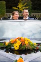 Brautpaar schaut aus Dachfenster vom Hochzeitsauto