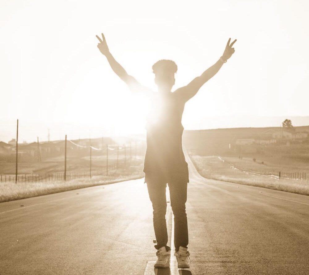 Junger Mann mit ausgestreckten Armen auf der Straße im Sonnenuntergang