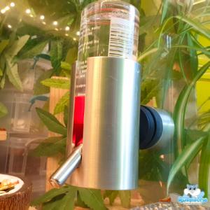 foto van een aluminium drinkfleshouders met drinkfles erin voor een hamster of dwerghamster