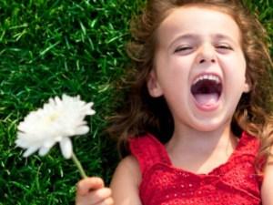 Niña sonrie en el césped con flor en la mano