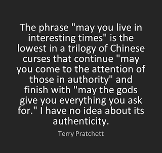 "White text on a black background that reads ""The phrase 'may you live in interesting times' is the lowest in a trilogy of Chinese curses that continue ""may you come to the attention of those in authority"" and finish with ""may the gods give you everything you ask for."" I have no idea about its authenticity. -Terry Pratchett."""