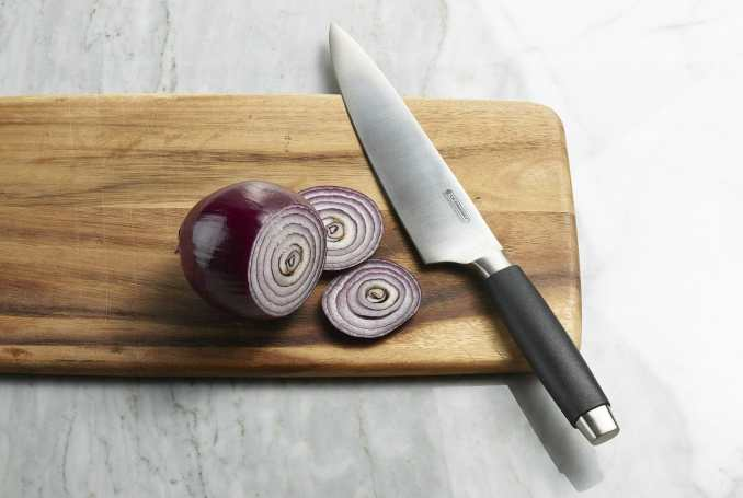 An onion on its side on a cutting board, with a few slices cut off and fanned slightly, the knife laid across the cutting board nearby.