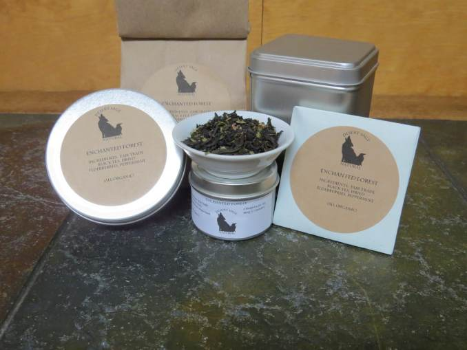 "A small white bowl, perched on top of a tea sample tin, filled with a blend of black tea, peppermint, and elderberries. Arrayed around it are a larger sample tin, a bag, a tea tin, and an origami packet of a size to hold a teabag. The labels read: ""Enchanted Forest, Organic Ingredients: Fair Trade Black Tea, Dried Elderberries, Peppermint, (All Organic)"" The table they sit on is a textured green stone. The background is a light woodgrain."
