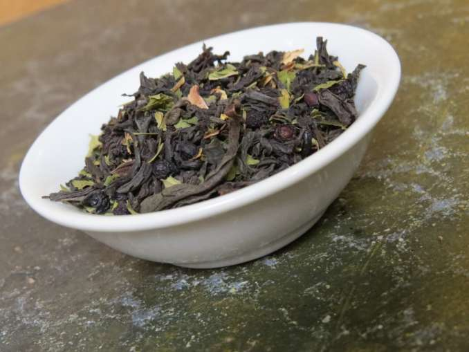 Close-up image of a small white bowl filled with a blend of black tea, peppermint, and elderberries. It is tilted and angled so that you have a clear view of the tea. It is set on a textured green stone table.