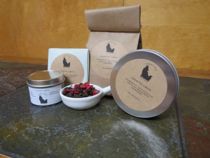 "A small white bowl shaped a bit like a pan filled with green tea and bits of freeze dried raspberries, circled by 2 tea tins, an origami packet with a teabag inside, and a bag of tea. The labels read ""Galactic Green, Organic Ingredients: High Mountain Green Tea, Freeze-dried Raspberries, (All Organic)"
