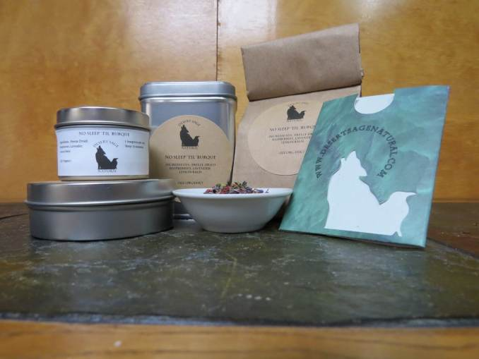 "A small white bowl full of a blend of freeze-dried raspberries, lemon balm, and lavender. Around the bowl is an array of tea tins, a bag of tea, and a cardboard slipcover holding a single teabag. The labels read: ""No Sleep 'Til 'Burque, Ingredients: Freeze-Dried Raspberries, Lavender, Lemon Balm, (All Organic)"""