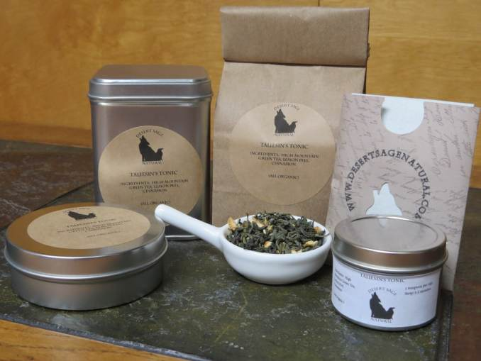 """A small white bowl full of a blend of green tea, cinnamon, and lemon peel, surrounded by an array of tea tins, a bag of tea, and a small paper packet that could hold a single teabag. The labels read: """"Taliesin's Tonic, Ingredients: High Mountain Green Tea, Lemon Peel, Cinnamon, (All Organic)."""""""