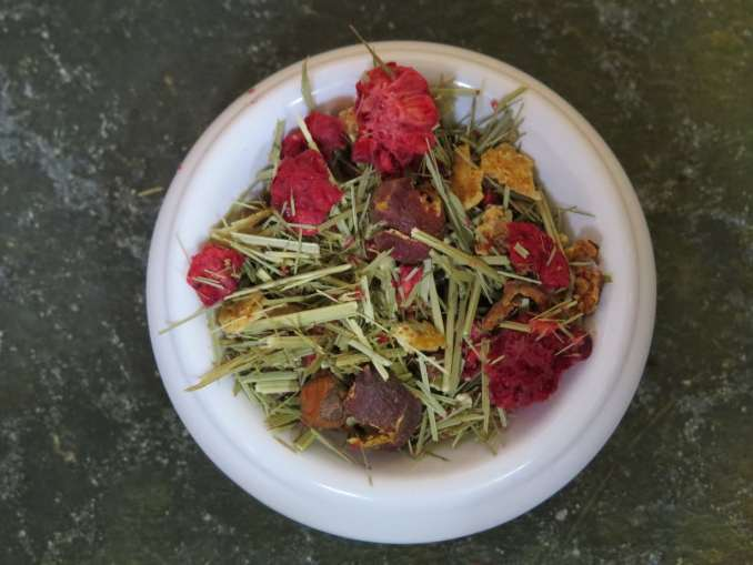 Small white bowl full of a blend of lemongrass, hawthorn berries, lemon peel, and freeze-dried raspberries. It is shot from above, fairly close, so that you can get a good look at the tea. The background is a textured green stone.