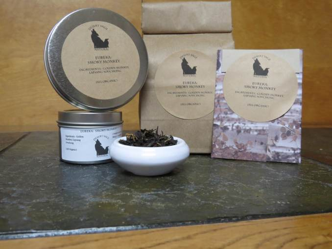 """A small white bowl full of a blend of golden and black teas. It is surrounded by a couple of tea tins, a bag of tea, and a rectangular packet that could hold a teabag. The labels read: """"Eureka: Smoky Monkey, Ingredients: Lapsang Souchong, Golden Monkey, (All Organic.)"""