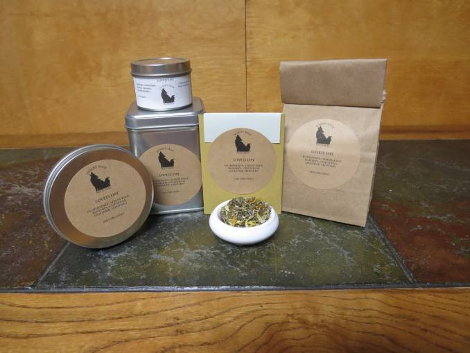 """A small white bowl full of a blend of lemon balm, rosehips, calendula, lavender, and eleuthro. It is surrounded by a variety of tea tins, a bag of tea, and a small rectangular packet that could hold a single teabag. The labels read """"Lovely Day"""" and have the list of ingredients, also noting that they are all organic."""