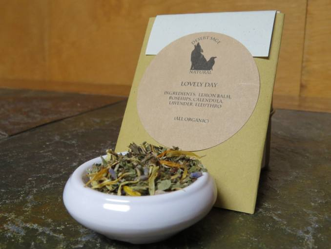 """A small white bowl with a blend of lemon balm, rosehips, calendula, lavender, and eleuthro. It is set on a green textured stone table. Behind it is a rectangular packet. The label on the packet reads: """"Lovely Day, Ingredients: Lemon Balm, Rosehips, Calendula, Lavender, Eleuthro, (All Organic)"""""""