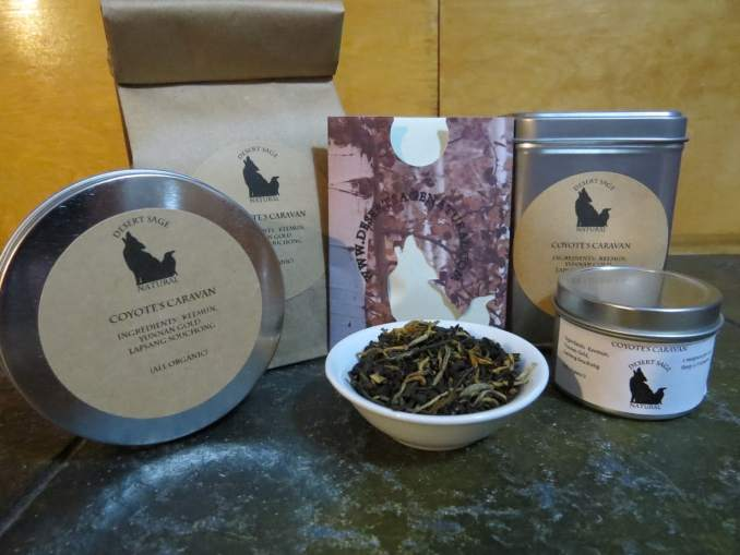 "A small white bowl filled with a blend of black teas. It is surrounded by an array of tea tins and a bag of teas. The labels state ""Coyote's Caravan, Ingredients: Keemun Black, Yunnan Gold, Lapsang Souchong All Organic."""