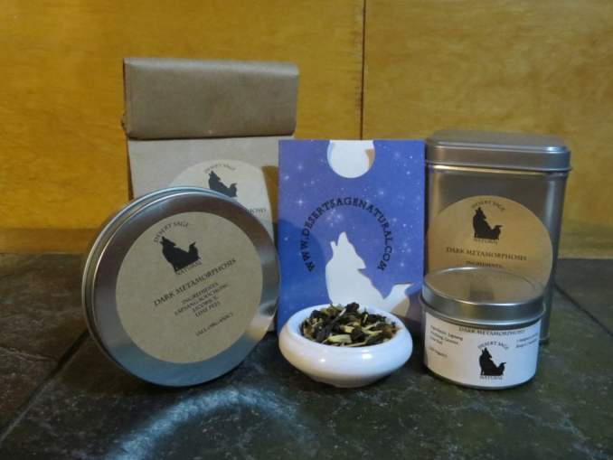 "A small white bowl full of a blend of lapsang, licorice, and lime peel is in the center of an array of tea tins, a bag of tea, and a small paper packet with the desert sage natural logo on it that would hold a teabag. The labels read: ""Dark Metamorphosis, Ingredients: Lapsang Souchong, Licorice, Lime Peel (All Organic)"""