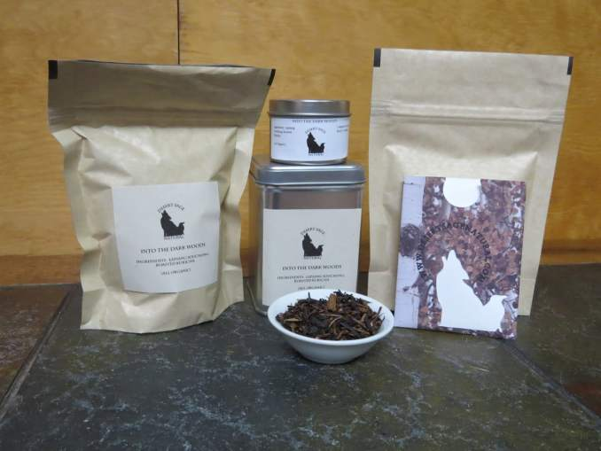 """A small white bowl filled with a combination of roasted kukicha and lapsang. Behind it are 2 tea tins, a couple of bags of tea, and a rectangular packet that could hold a teabag. The labels read: """"Into the Dark Woods, Ingredients: Lapsang Souchong, Roasted Kukicha, All Organic."""""""