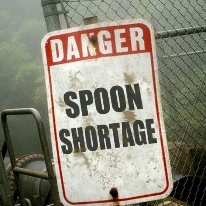 "beaten up sign next to a fence and chair that both look battered. The sign says ""Danger SPOON Shortage"""