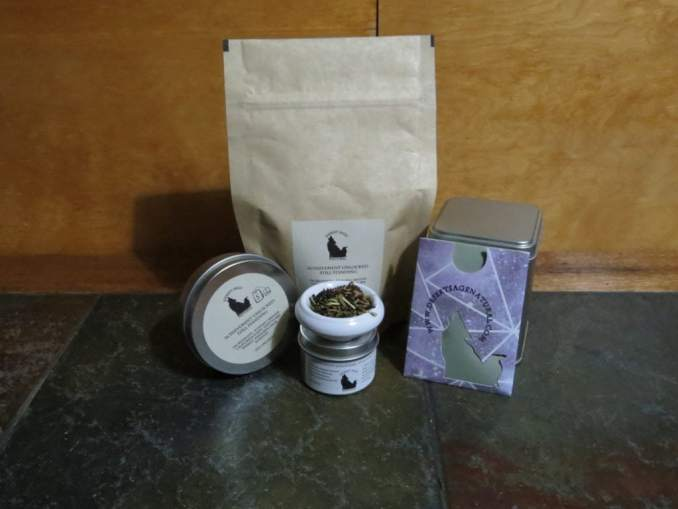 A small white bowl filled with a blend of tea and herbs set on top a small tin. Behind it is a large bag of tea, to the sides other tea tins and a small rectangular packet of a size to hold a teabag. The labels read: Achievement Unlocked: Still Standing, Ingredients: Russian Caravan, California Poppy, Hawthorn berries, Rosehips, Passionflower (All organic)