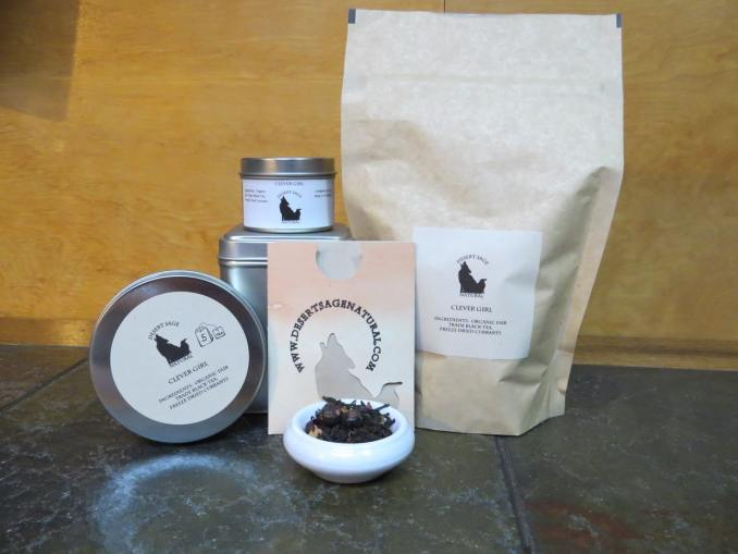 "Small white bowl full of a blend of black tea and freeze dried currants. Behind it is an array of tea containment objects, various tins, a bag, and a small rectangular packet that could hold a teabag. The labels read ""Clever Girl Ingredients: Organic Black Tea, Freeze Dried Currants"""
