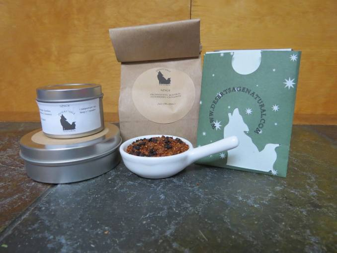 """A small white bowl full of a combination of rooibos, dried elderberries, and cinnamon. it is surrounded by two small circular tea tins, in different sizes, a bag of tea, and a small rectangular packet with a cutout of the Desert Sage Natural logo that could hold a single teabag. The labels read """"Syzygy, Organic Ingredients: Rooibos, Elderberries, Cinnamon"""""""