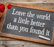 """A small chalkboard, with roses in the corner, written on it is """"Leave the world a little better than you found it."""""""