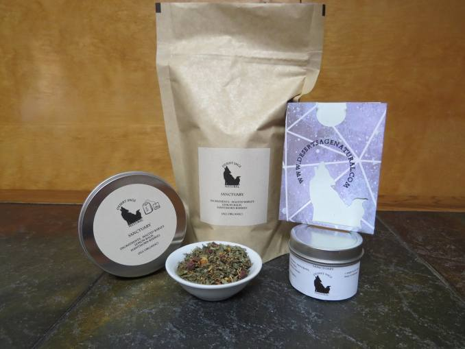 "A large bag of tea, with a circular sample tins to either side, the smaller of the two has a purple packet with the Desert Sage Natural Logo as a cutout balanced on top.  In front of the array is a small white bowl full of a blend of hawthorn berries, lemon balm, and barley.  The labels read:  ""Sanctuary, Ingredients:  Malted Barley, Lemon Balm, Hawthorn Berries, All Organic."""