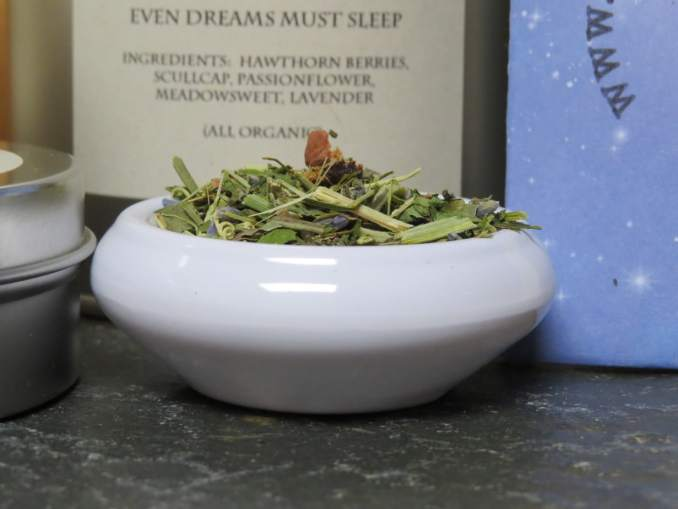 """A close-up shot of a small white bowl of tea, full of a blend of lavender, hawthorn berries, and green herbs.  Behind it you can just make out the words on a slightly blurred label """"Even Dreams Must Sleep, Ingredients:  Hawthorn berries, Scullcap, Passionflower, Meadowsweet, Lavender, (All Organic)."""""""