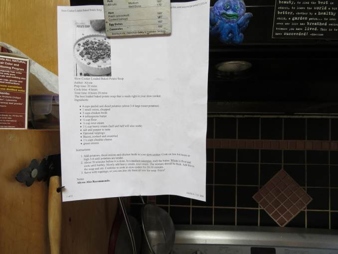 A printed out recipe attached by magnet to a stove hood.  Next to it is a child-painted purple, blue, and green octopus.