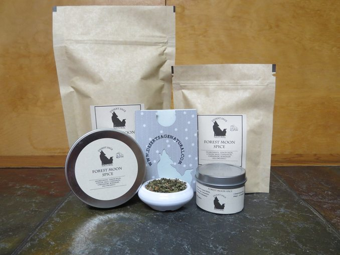 """An array of bags and tea tins and a small paper packet, arrayed around a small white bowl full of a blend of spices and herbs.  The bags and tins are labeled """"Forest Moon Spice."""""""