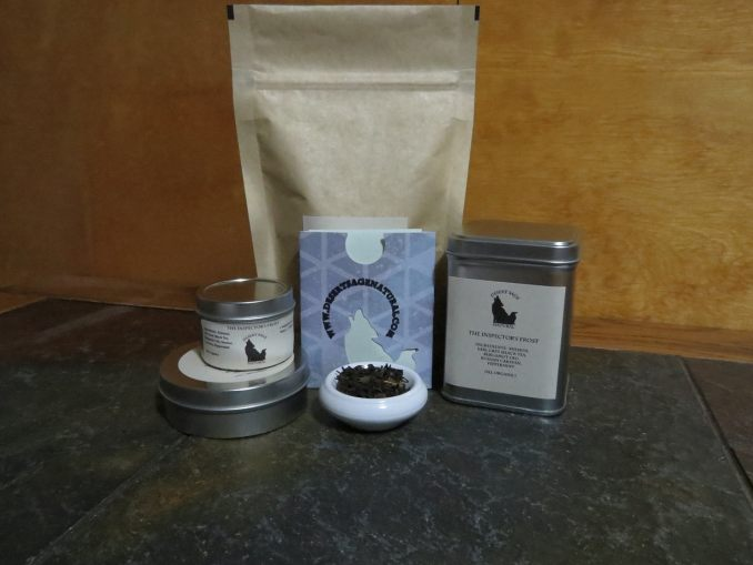 """A bag of tea, a tall tin of tea, and two round tins of tea, one large, one small, arrayed around a small white bowl full of a mix of teas and peppermint.  The labels read """"The Inspector's Frost.'"""