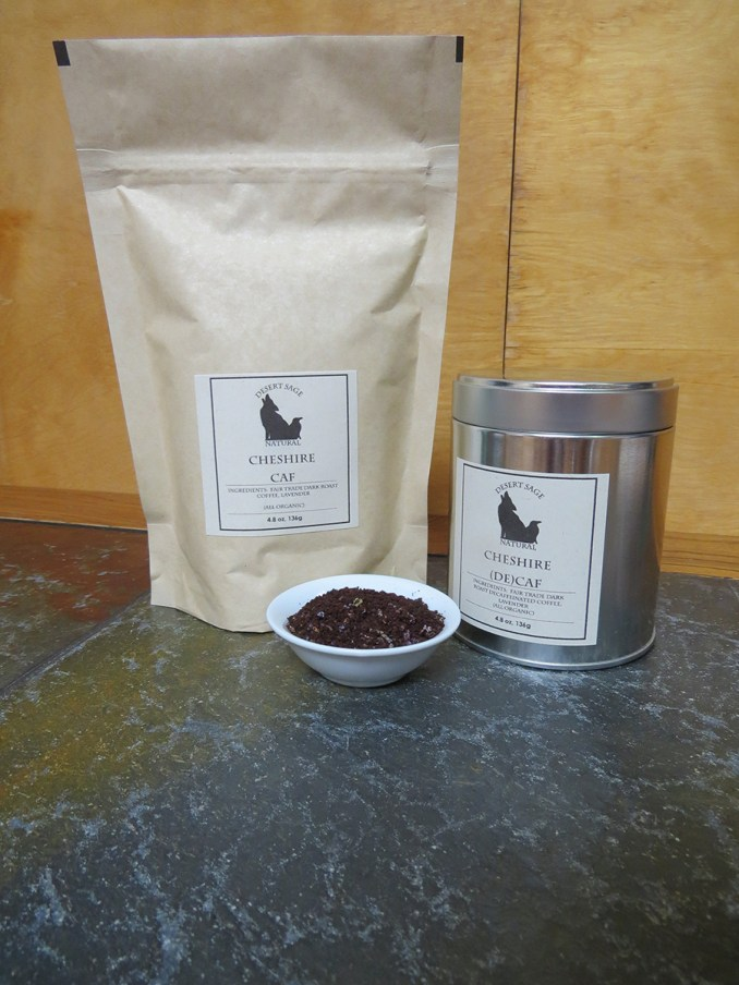 A bag labeled Cheshire Caf and a tin labeled Cheshire (De)caf, sitting to either side of a small white bowl filled with a blend of lavender and dark roast coffee.