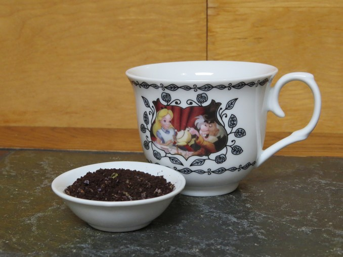 A mug featuring Alice and the Mad Hatter sharing tea, settled on a textured stone table next to a small white bowl full of a blend of dark roast coffee and lavender.