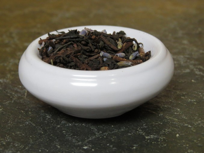 A small white bowl of tea, set on a green textured stone table.  The bowl is full of a blend of lavender flowers, roasted kukicha, and lapsang souchong.