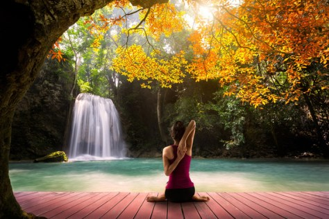 Young woman in yoga pose sitting near watefall, Rear view