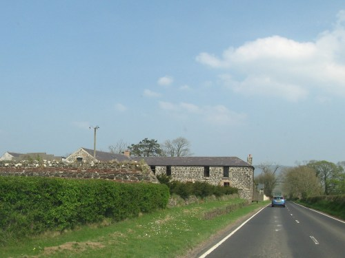 Well maintained stone house with a slate roof. Brick around the windows.