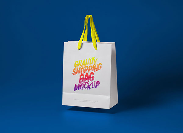 Two blank grey and white eco friendly paper bags on light surface. 50 High Quality Free Shopping Bag Mockup Psd Files