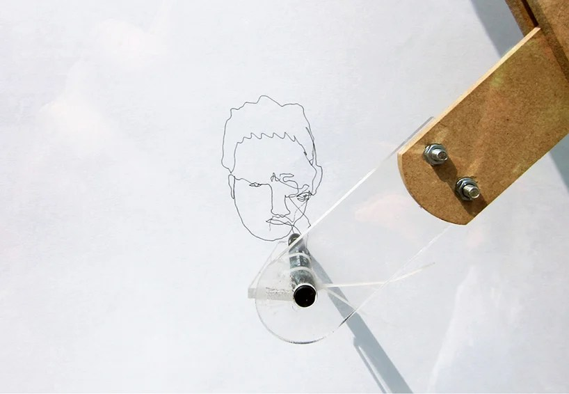 portrait pantograph invites public to draw faces on a window