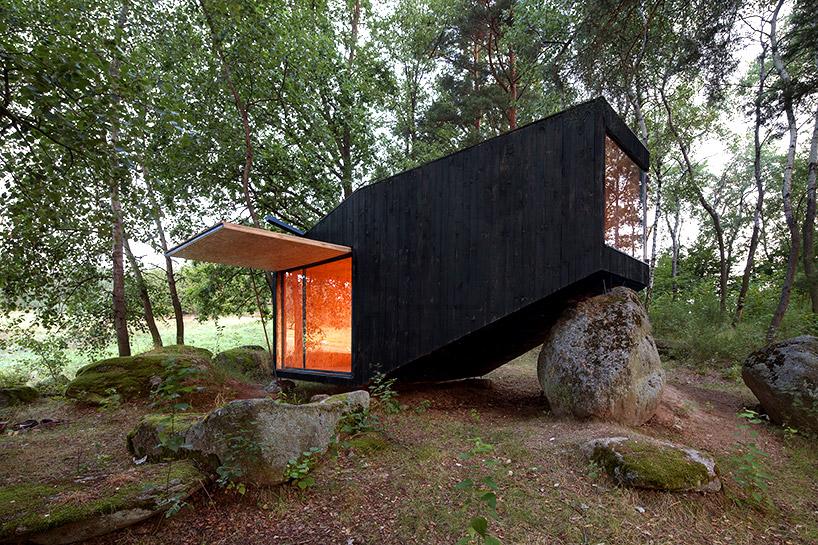 uhlik architekti balances private forest retreat on top of boulder
