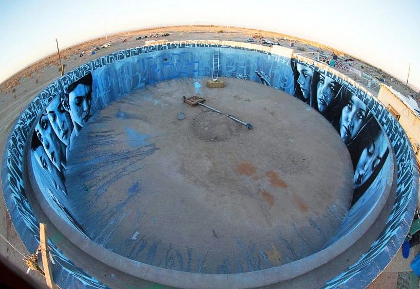 artists paint circular mural inside abandoned water tank in the desert