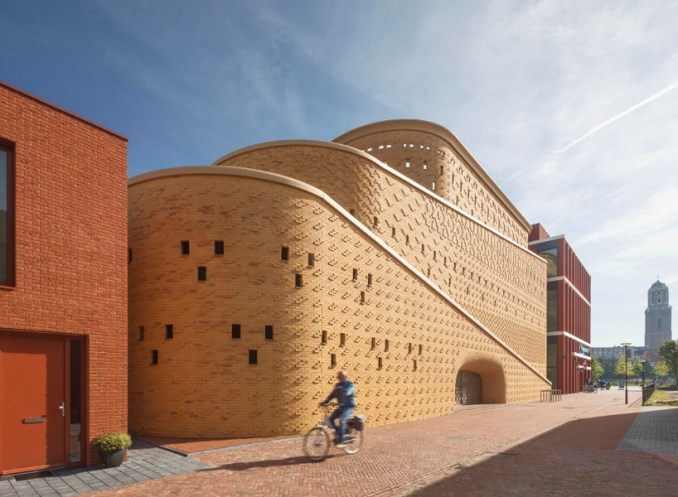 eastern hues and patterns adorn the brick facade of this car park by
