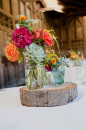 Garrafas de vidro servindo de vasos de flores, decorando mesa