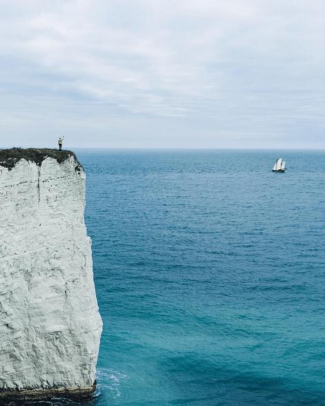 Aparece acenando para uma embarcação desde um penhasco do condado litorâneo de Dorset, na costa sul da Inglaterra.