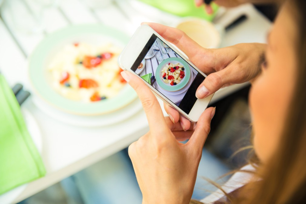 Portrait of a woman making photo of food on smartphone in restaurant
