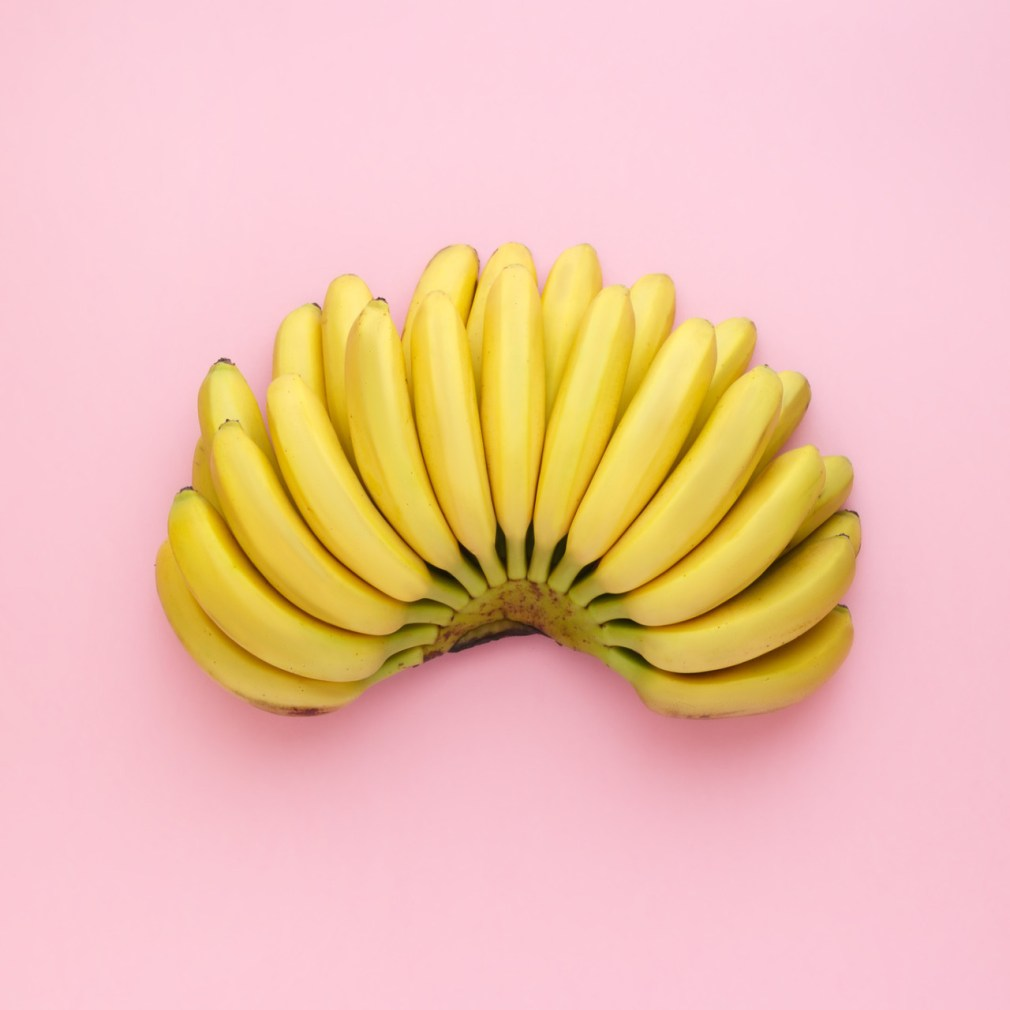 Top view of ripe bananas on a bright pink background. Minimal style.