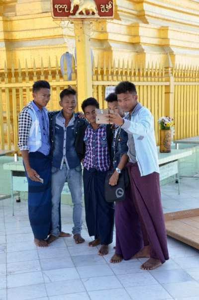 Young men taking selfies at a pagoda in Myanmar
