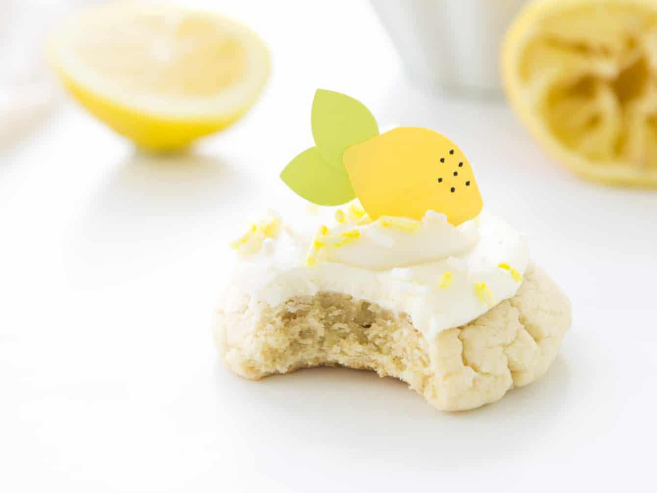 Lemon sugar cookie with cream cheese frosting with bite out of it.