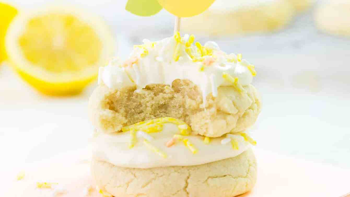 Piping bag and tip piping cream cheese frosting onto lemon sugar cookie.