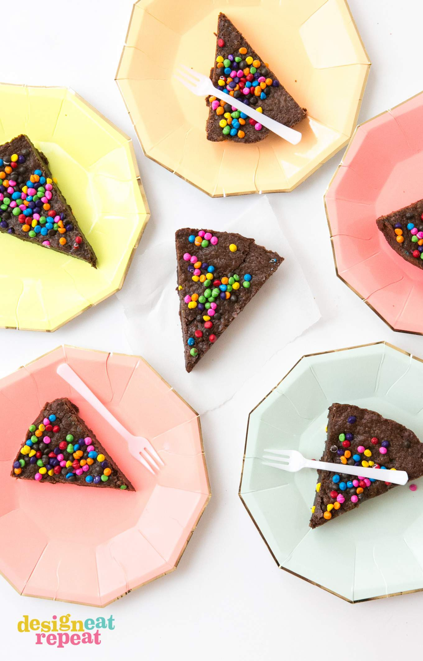 Slices of brownie pie on colored paper plates.