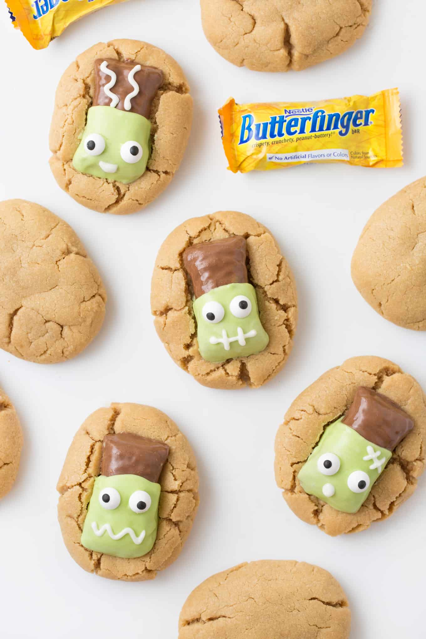 How fun are these Frankenstein cookies? Simply dip Butterfinger Fun Size Candy Bars into melted almond bark to turn normal peanut butter cookies into adorable Frankenstein cookies! A perfect Halloween treat idea to make with the kids for parties, class treats, or more! #Halloween #HalloweenCookies #Butterfinger | www.DesignEatRepeat.com