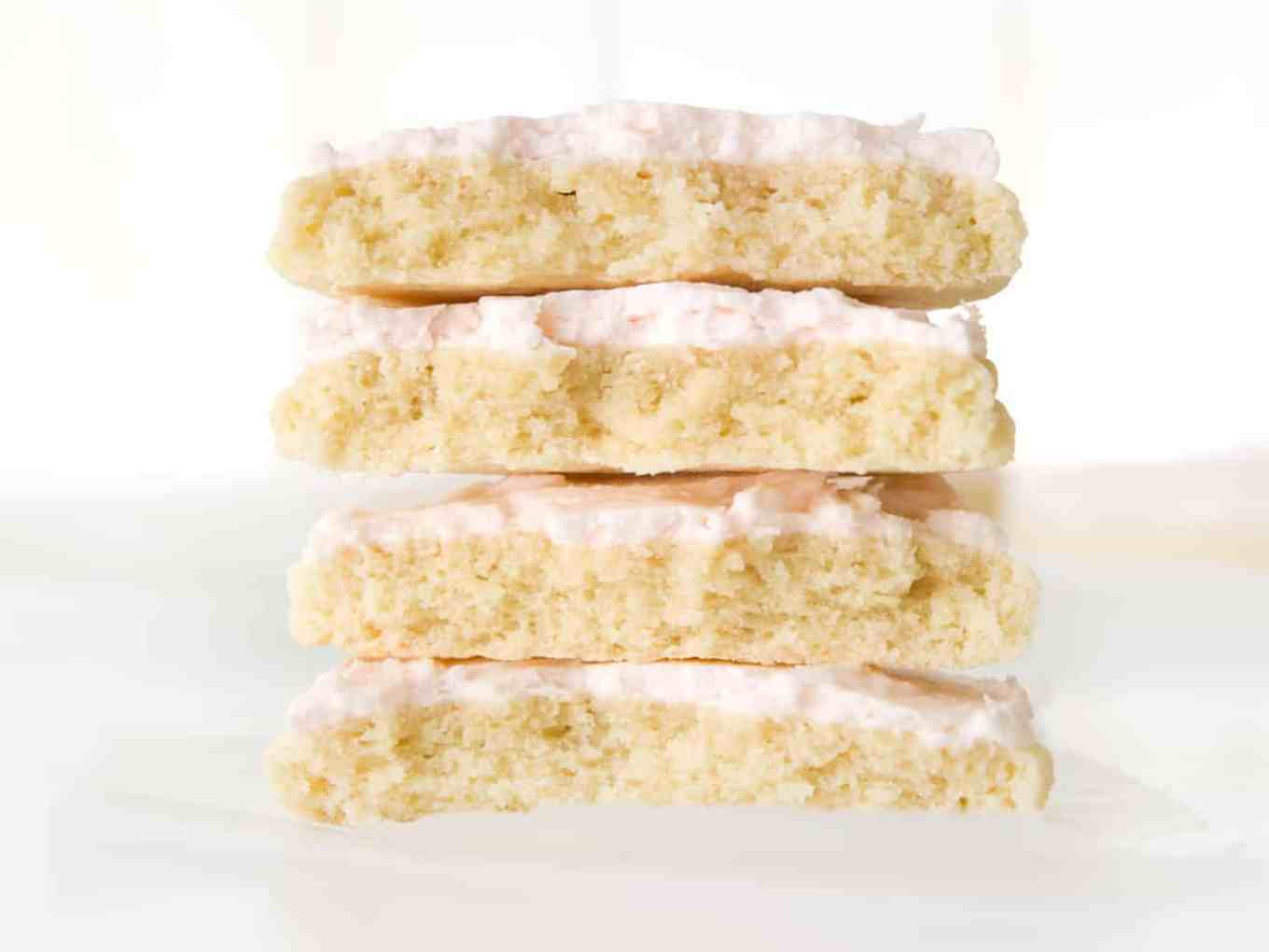 Stack of two large sugar cookies with pink frosting, cut in half.